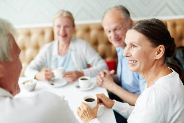 Group of senior companions sitting by table in cafe and having talk by cup of coffee